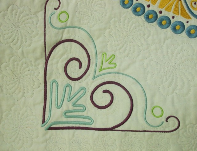 "We added corner embroideries around the big circles of ""wedges"". Note the Acufil Embroidered quilting in the background as well as a little free motion quilting."