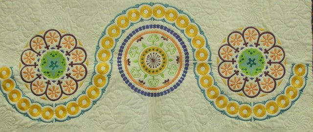"Next came the section below the ""pizza"". This is made up of 3 large circular embroideries and surrounded by 6 quarter circles. Again, there was NO WAY I would have attempted this without my trusty JANOME CLOTHSETTER & printed templates to mark out the fabric & hoop up accurately.  Colour choice was also a critical factorfor Debbie & I: we spent quite a bit of time trying out various combinations to achieve the overall result we were looking for.  Note: this section was 9 hoopings."