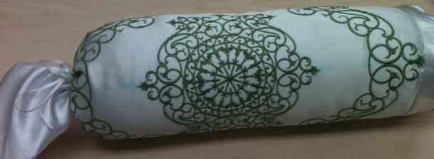 Not the best lighting on this pics, sorry. It shows 2 of the brand new designs which I stitched onto white satin & made into a neck roll pillow.  The designs are reminiscent of wrought iron work and stitch out just beautifully - fine little satin stitches are a breeze for our new JANOME MC 15000!!