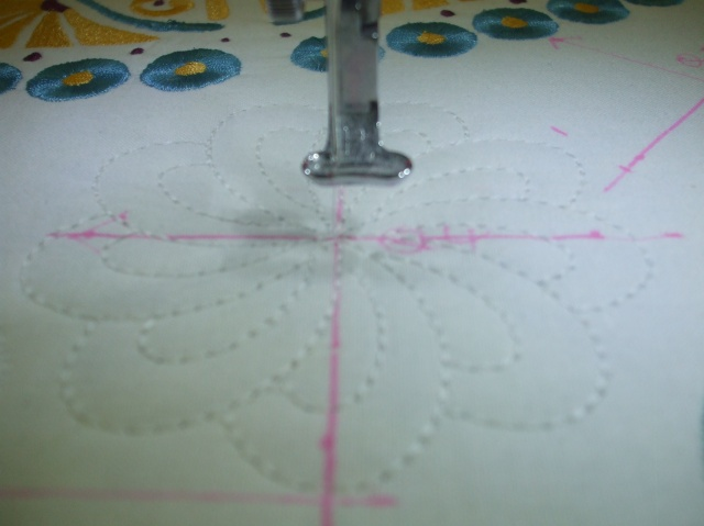 HERE IS A CLOSE UP OF THE TEMPLATE MARKING ON THE FABRIC AND LINING UP THE NEEDLE IN THE CENTER OF THE CROSS HAIR BEFORE QUILTING THIS DESIGN IN THE ACUFIL MAGNETC CLAMP HOOP