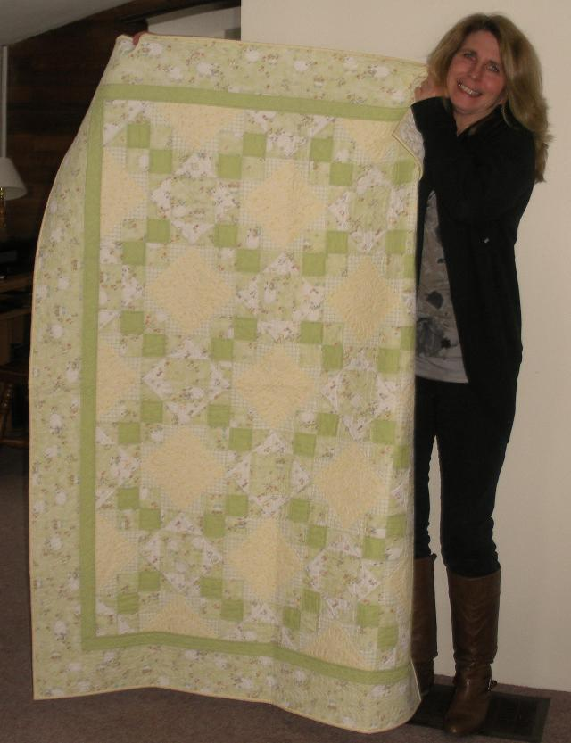 Amy holding up a delightful baby quilt. The free motion quilting on this is also just beautiful. See pic below of a close up.