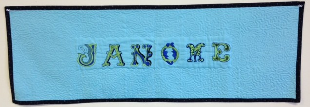 Decided to keep it simple and just have the word JANOME  embroidered surrounded by Acufil stippling. Banner was bound using the JANOME QUILT BINDER SET