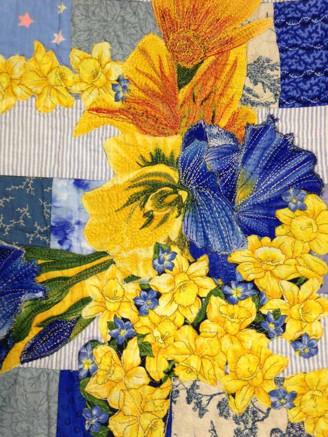 a close up showing the thread painting over top simple fussy cut flowers from print fabric.