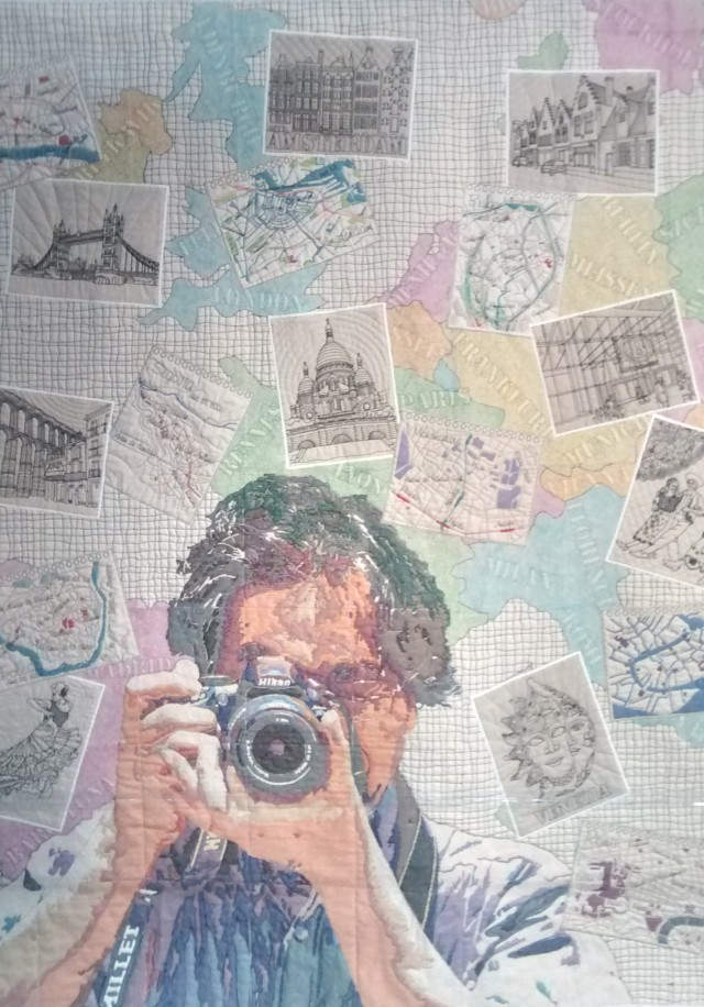 """This quilt is called """"Photographer Darling"""" by Noriko Nozawa of Chiba City, Japan. It is a compilation of a railtrip through Europe where her husband was the photographer - he is honoured here. Noriko has won the Fairfield Master Award for Contemporary Artistry with this quilt.  Close up in next pic - CHECK OUT the thread work!"""