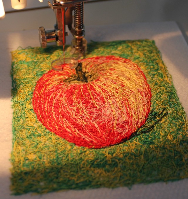 A little goes a long way: dark stitches add shadow to the stem and to the right side of the apple
