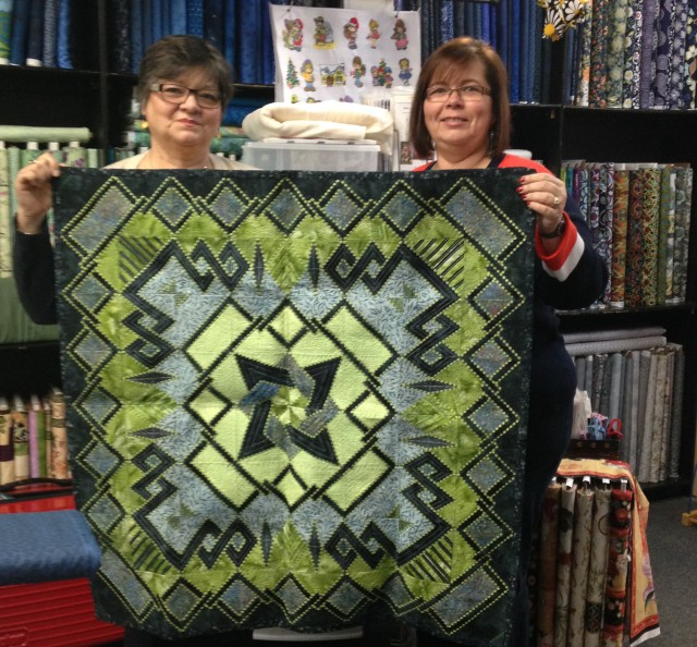 Shirley (right) shows one of the embroidered quilts she has on display in her store: Ultimate Sewing Center, Oshawa