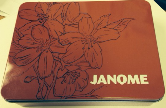 The red tin measures 8 x 6 inches with pretty flower sketch & white JANOME logo