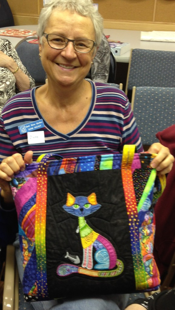 Dianne is proudly holding the bag she made with funky cats.