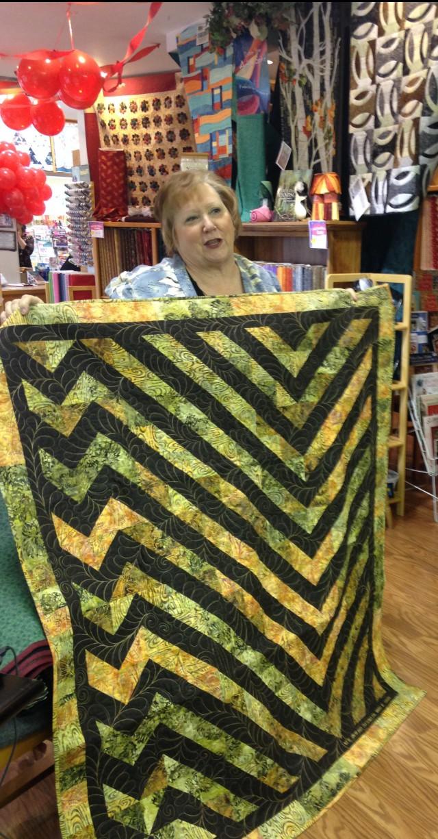 "Donna mae holds up her quilt which was made totally with left overs from another project and free motion quilted with feathers......Ihave named Donna Mae a ""free motion Queen"" as she does such lovely stitching"