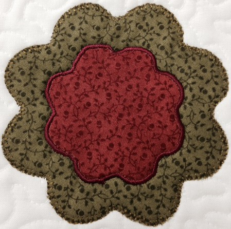 Simple flower shape use to cut the fabric, raw edge fusible web applique with satin stitching on the red flower & applique/blanket stitching on the green outer flower.  Arrange a bunch of flowers & leaves? free motion some stems & voila....you have a spring posie!