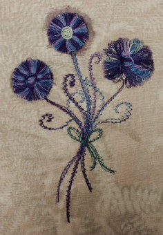 Debbie made this pretty little posie: embroidered fringe flowers with free motioned stems & bow.