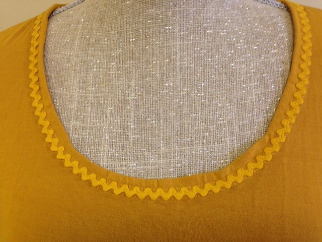 Stay tape was fused to inside edge which was turned over to wrong side. A triple coverhem  was stitched around the neck opening ON TOP OF a piece of matching ric-rac. Hold the ric-rac & folded hem edge in position with Clover clips or pins.