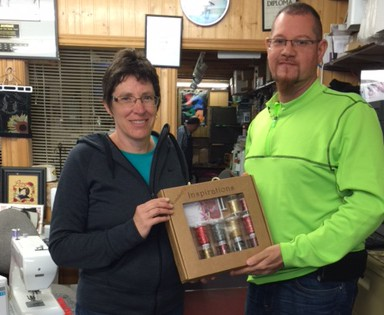 Mark of Sew & save, Stratford, Ontario handing over the box of Wonderfil Threads to Bev.