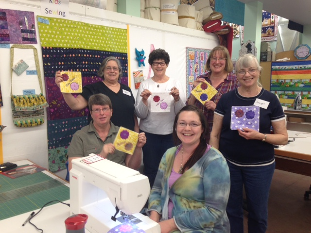 another group of Quilting workshop ladies displaying their mug rugs.