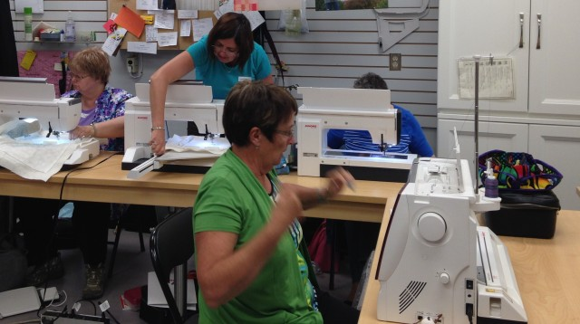 Janome customers busy learning about their top of the line sewing & embroidery machines