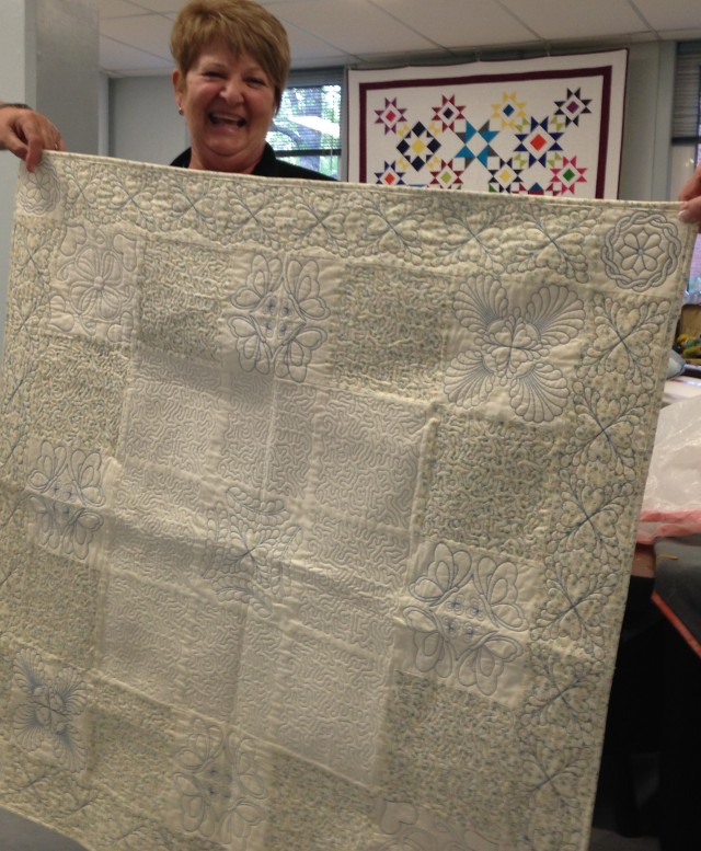 An excited and proud, Linda shows off her quilt which was quilted using our Janome Acufil quilting system on her Janome MC15000