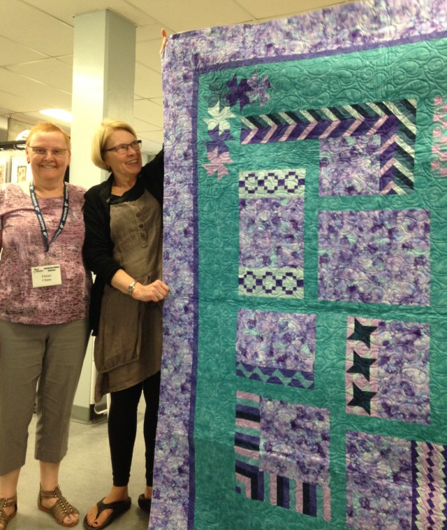 "Most evenings after dinner, there is a casual presentation ""Meet the teacher"". Here Wendy (right) holds up a Border design quilt made by Elaine (left). This was a class taught by Diane Janzen at the Conference in 2014 - Elaine was showing her finished project which was a sampler quilt made up of various different designs that can be used for borders on quilts. Many of these were completed and shown so it was a class very well received. Diane is a popular teacher."