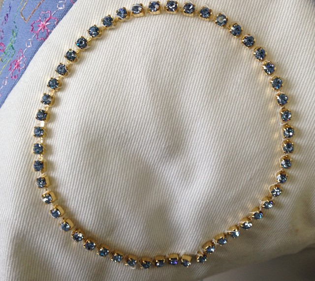 a close up of the pillow showing the use of the Circular attachment to apply a string of metallic & crystal beads in a circle.