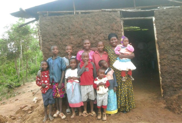 A Kenyan family clustered outside their home. I thought you might like to see the mud hut - many who have never been to Africa or seen similar homes may be unfamiliar withthis type of dwelling: dirt floor, tree branches used for the structure which is then packed with mud which dries.