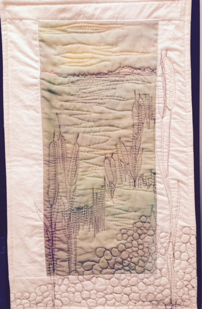 Slough with cattails by Anne Marie Irving, Kelvington, SK. who started to create an Art Quilt Journal I January 2015 where one gets to try different techniques. They are small quilts or wall hnagings. Anne Marie used fabric she has painted, free motion quilting and thread painting.