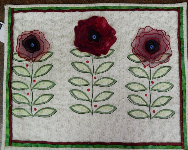 """Bev used built-in designs on her Janome MC15000 to create this lovely """"poppy"""" garden."""