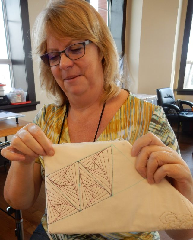And look at this great 3D effect created by another happy quilter - simply decreasing triangles inside a grid/block....all done with a ruler and free motion stitching