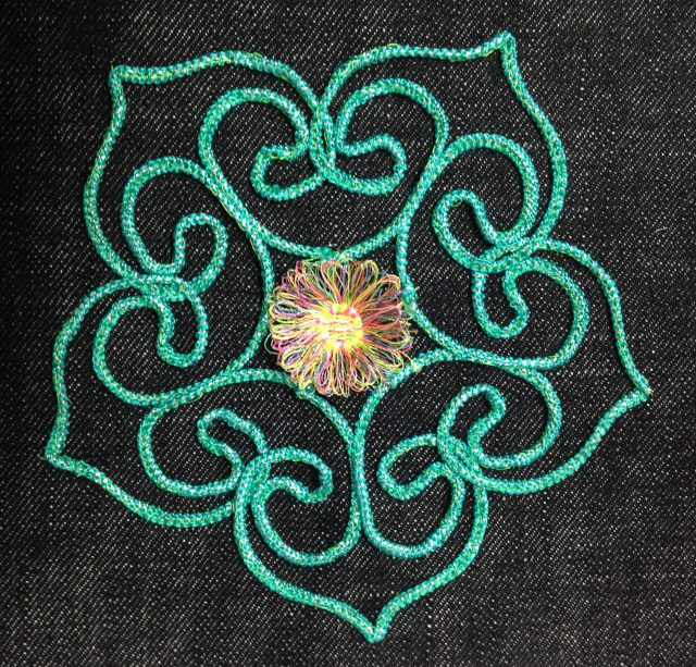 More embroidery couching with a fringe flower in the middle