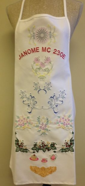 a bunch of built-in embroidery designs on the Janome 230E that have been stitched onto an apron.