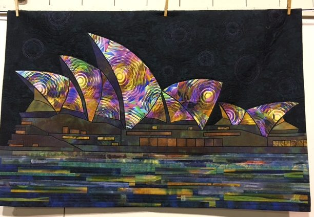 Another quilt she had on display. I cannot recall if this is part of the new book on buildings and architecture? We will find out next year. Obviously the Opera House in Sydney, Australia. This is showing a festival of some sort that shines brightly coloured lights onto the roof of the opera house and then there are reflections on the water of Sydney Harbour.