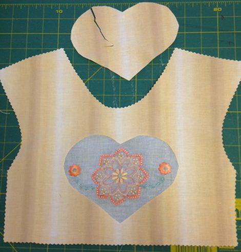 This embroidery design fro our brand new JANOME SKYLINE S9 SEWING AND EMBROIDERY MACHINE was stitched on a very thin sheer 100 lawn cotton. It had already been proved that the 3 sheets of flimsy water soluble stabilizer I had did not work! This time it was stitched on a firmer water soluble and once complete, was washed away completely. The dry fabric was pressed gently and placed behind the peach fabric. A heart template shape was marked on the fabric and stitched in place. The peach fabric heart was cut out as seen in this pic. In additon all the white lawn fabric outside of the heart shape was cut away at the back. BE GENTLE as this only has a straight stitch holding things in place and more sticthing is required.