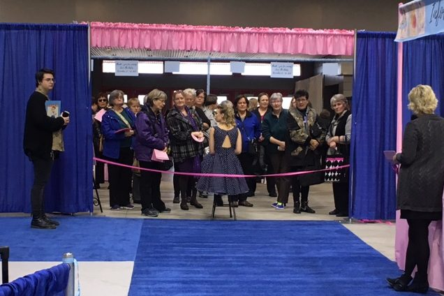 The cutting of the ribbon to open the first ever Love to Sew Expo. Debra Justice on the right and her son, Spencer, on the left just before the ribbon was cut. Show attendees are eagerly waiting to come in!