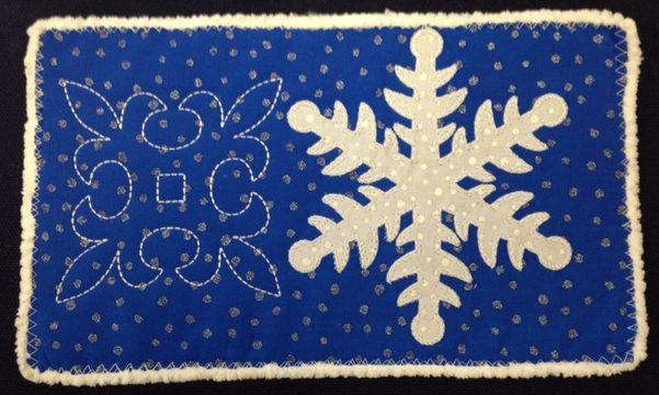 Snowflake wasa cut out with the Artistic Edge digital cutter and then appliqued-in-the-hoop with stitches digitized in the Simple Cutsoftware which comes included with the Artistic Digital cutter.