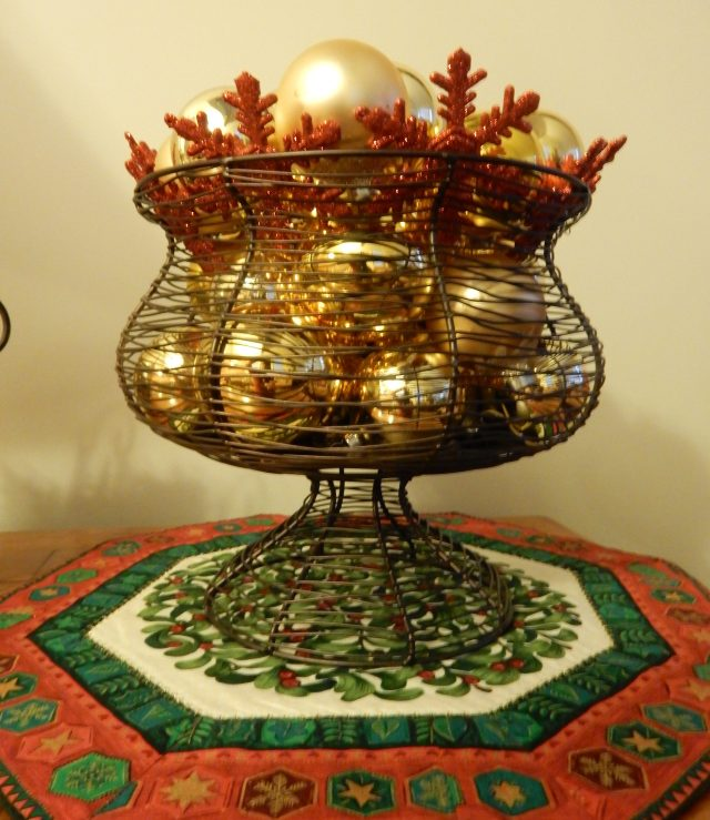 Christmas ornaments in a wire basket standing on a hexagonal table topper made years ago: use a border roint for the wide hexagon border and use an embroidery, applique or fussy cut a fabric design for the center part of the top.