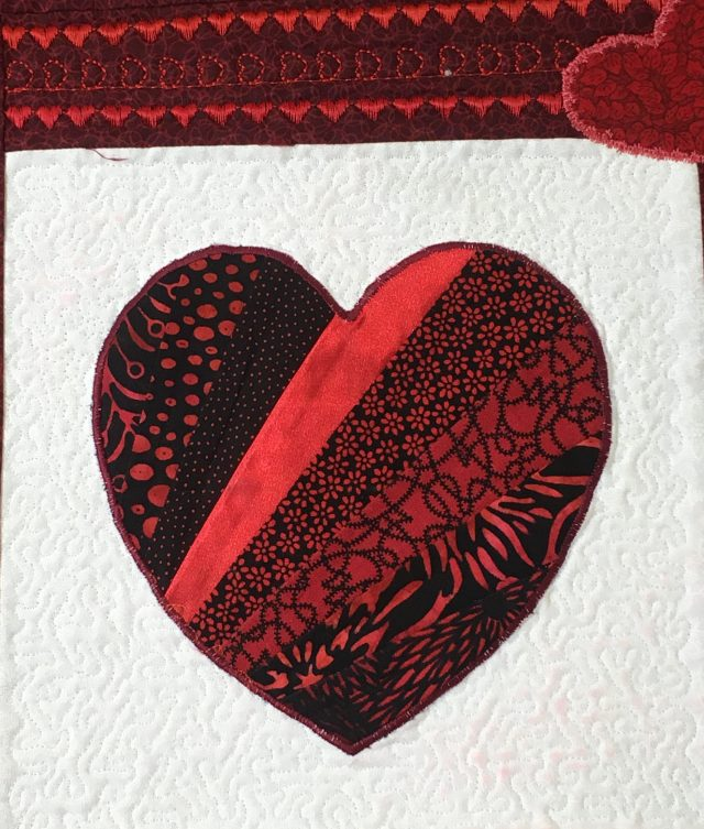 raw edge machine applique, micro stippling aroundthe heartusing Janome Digitizer MBX Ambiance quilting function + heart dec stitching above in the border