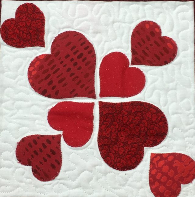Raw edge fusible web applique, echo/outline quilting + free mtoion in between the hearts.
